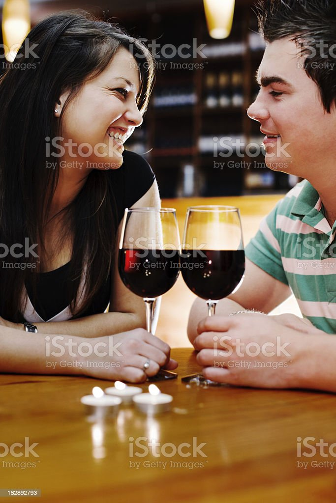 Happy young couple smile at each other over red wine royalty-free stock photo