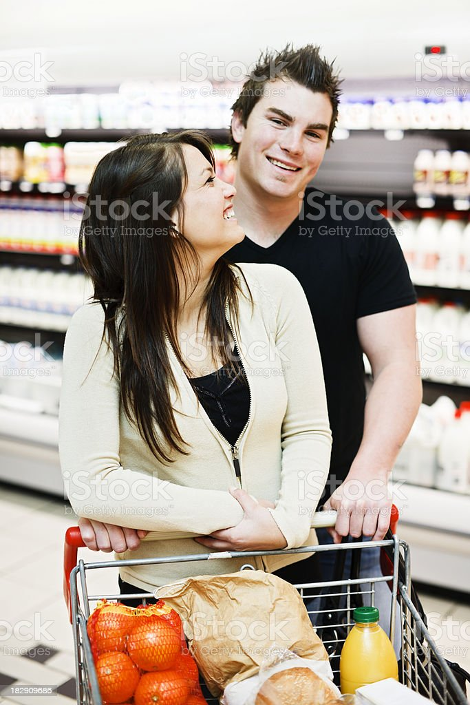 Happy young couple smile  in the supermarket dairy aisle royalty-free stock photo