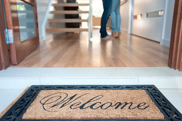 happy young couple standing inside their new house - estate agent sign stock photos and pictures