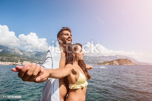 Happy young couple standing on a cliff and holding hands.