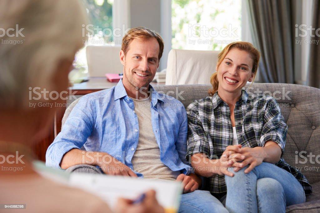 Heureux jeune couple prenant conseils financiers à la maison photo libre de droits