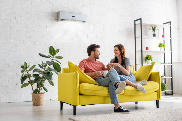 happy young couple talking and holding cups while sitting on yellow sofa under air conditioner at home stock photo