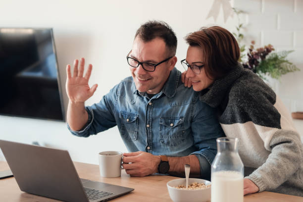 glada unga par pratar genom datorn med videochatt. par vinkar på kameran hemma - video call bildbanksfoton och bilder