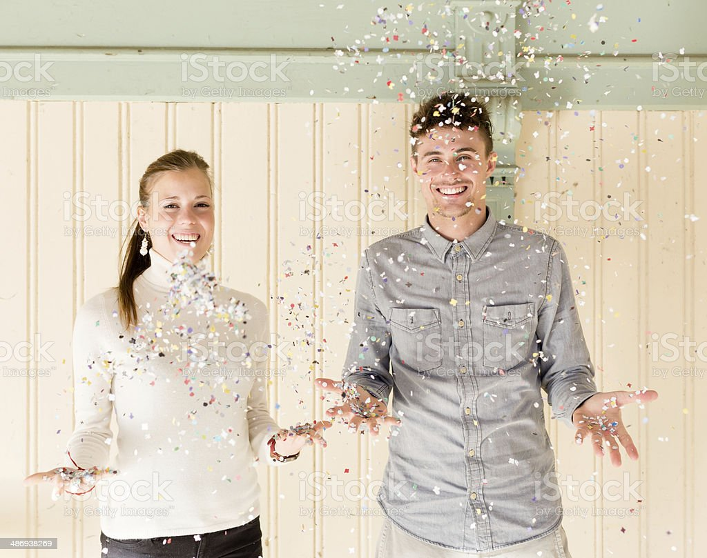 Happy young couple throwing confetti royalty-free stock photo
