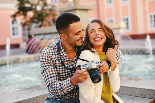 Happy young couple tourists making photos in the city stock photo