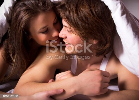 528422658 istock photo Happy young couple under blanket 185122105