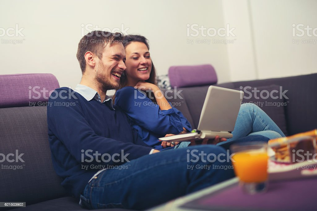 Happy young couple using a laptop at home and smiling foto stock royalty-free