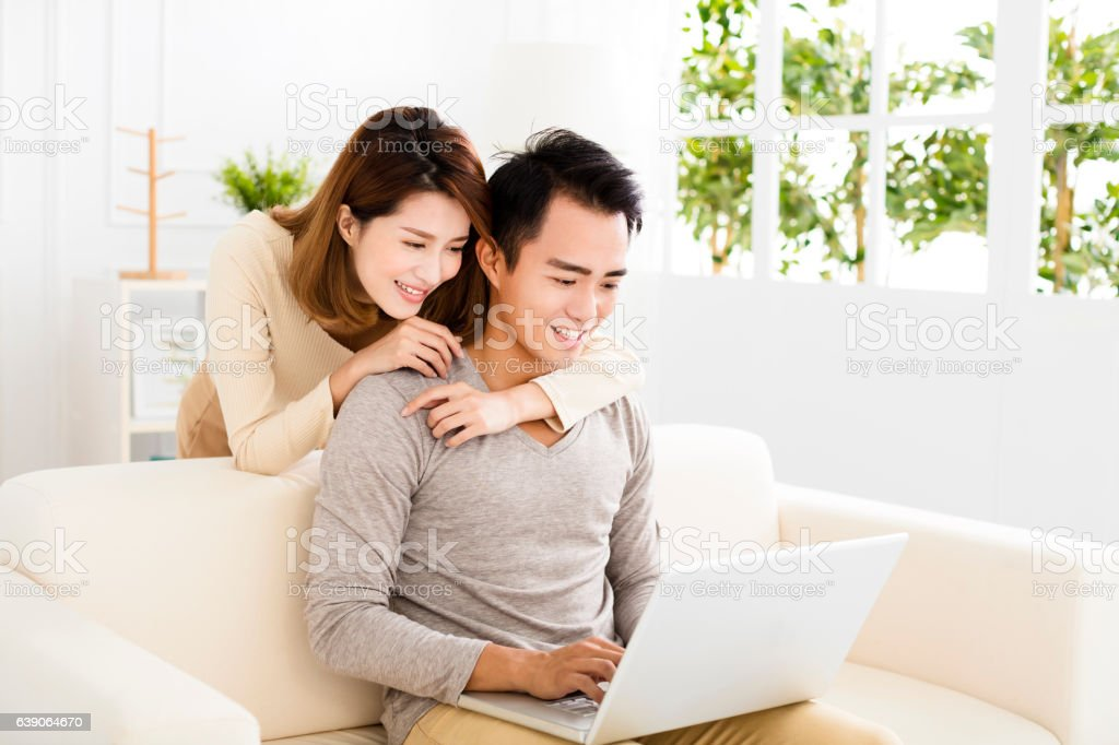 happy young couple using laptop on sofa stock photo