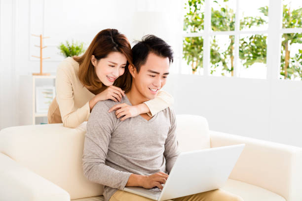 happy young couple using laptop on sofa圖像檔