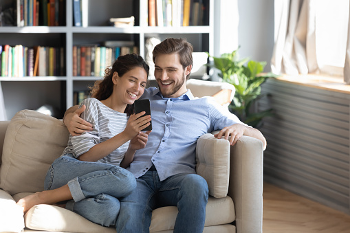 Smiling young couple sit relax on couch in living room have fun using smartphone together, happy Caucasian man and woman rest on sofa watch video on cellphone, make self-portrait picture on cell
