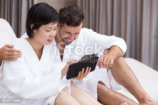 610769340istockphoto Happy Young Couple Using Tablet in Spa Salon 610771458