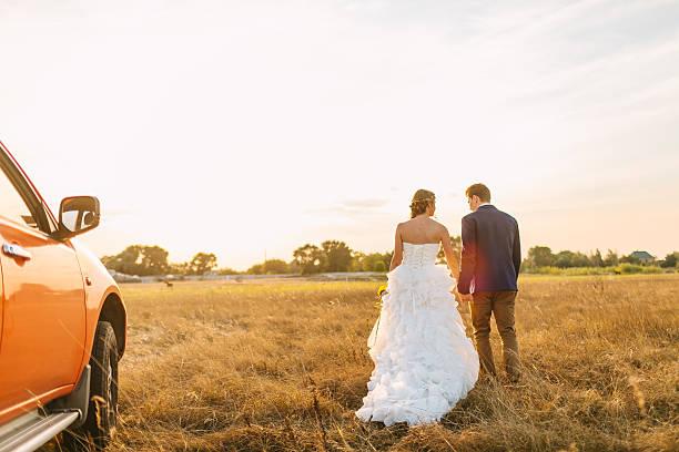 glücklich junge paar beim gehen im feld im sonnenuntergang. - hochzeitsfrisur twilight stock-fotos und bilder