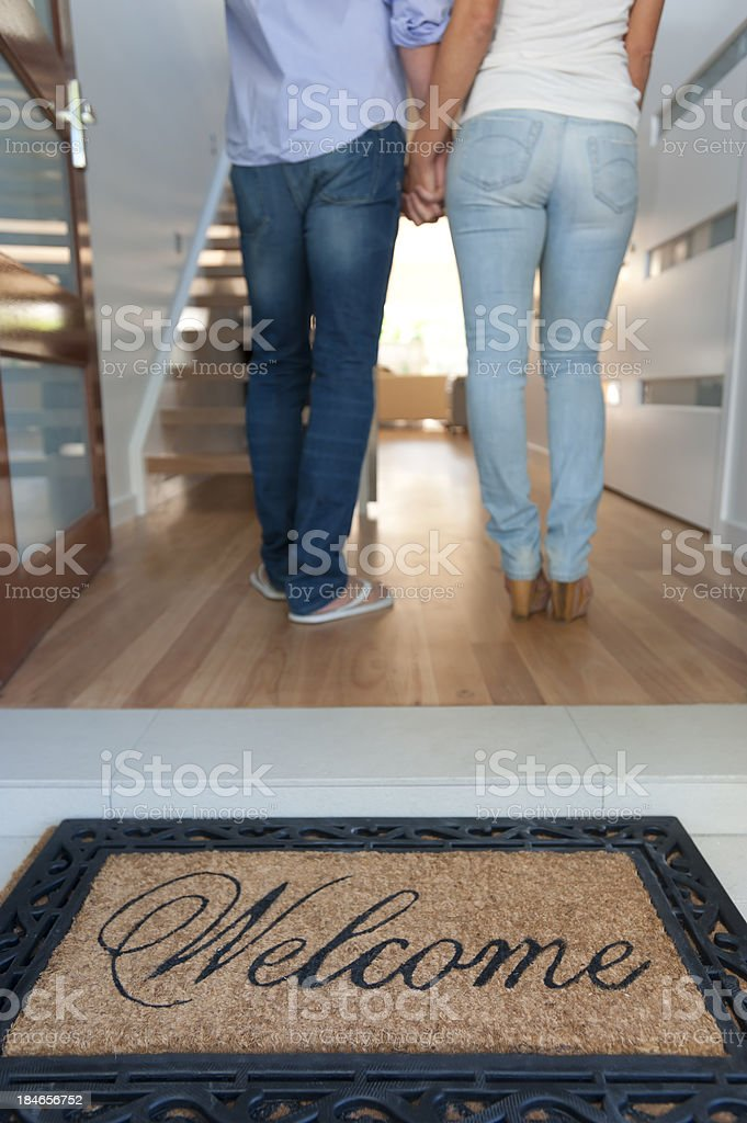 Happy young couple walking into their new house stock photo