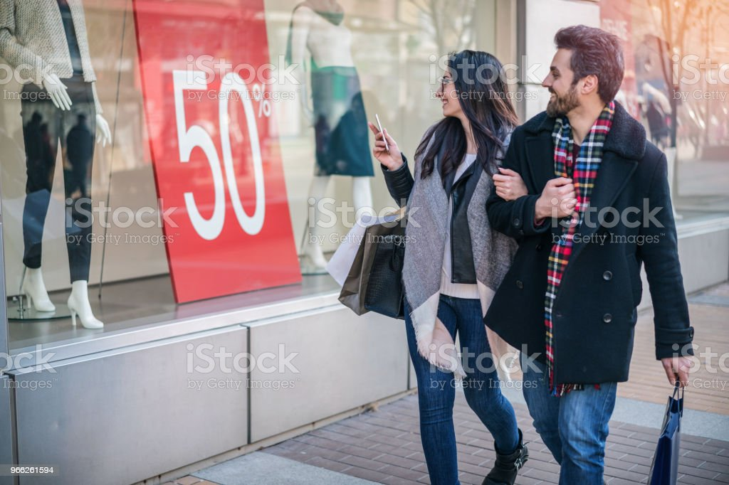Happy young couple walking on the street and staring at the shop window stock photo