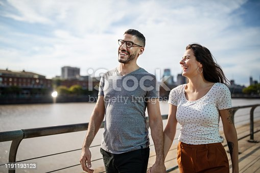 Happy young couple walking together on city boardwalk. Loving couple in casuals taking a walk on promenade outdoors in the city.