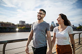 istock Happy young couple walking together on city boardwalk 1191193123