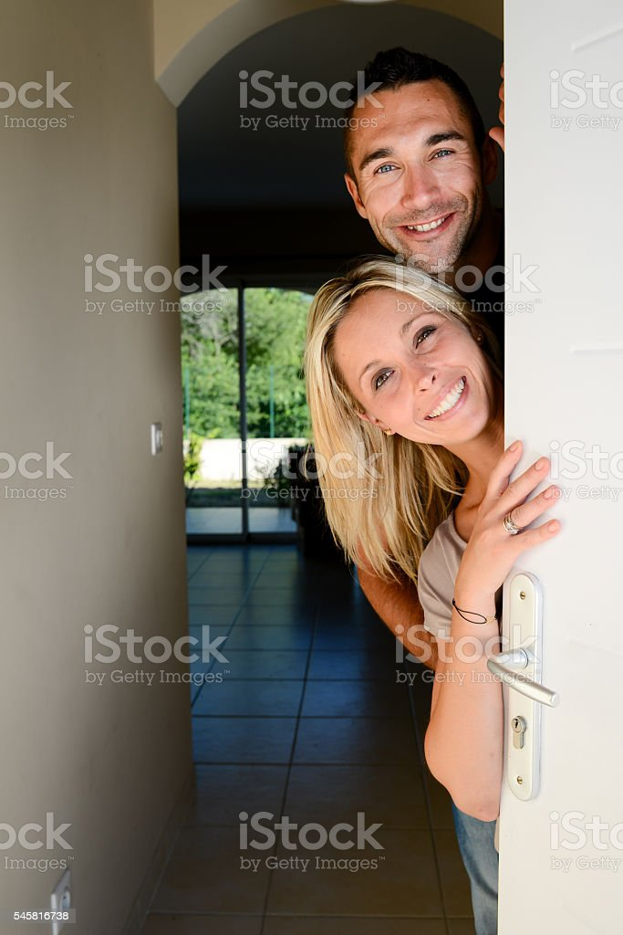 happy young couple welcoming friends at front door new house stock photo