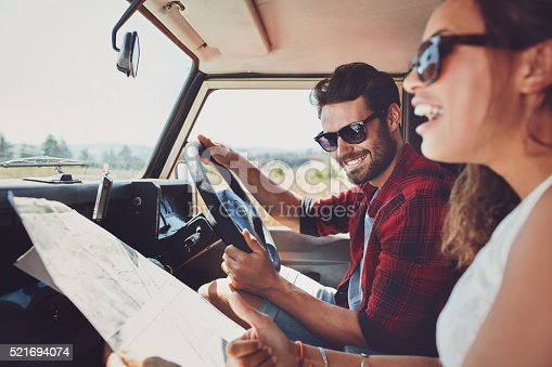 istock Happy young couple with a map in the car 521694074