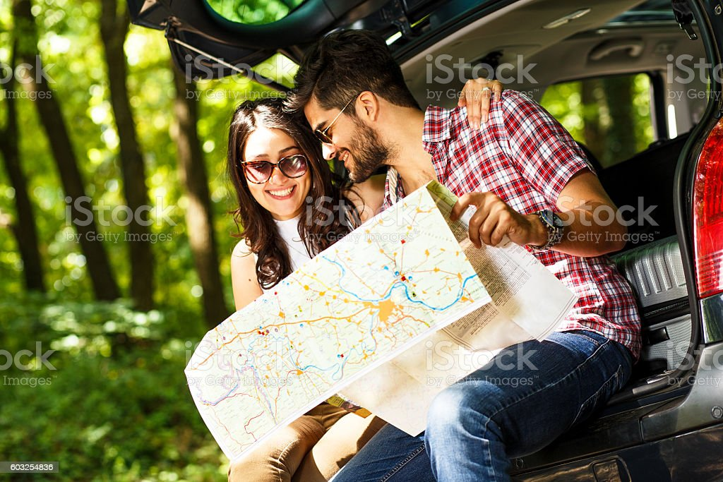 Happy young couple with a map in the car. stock photo
