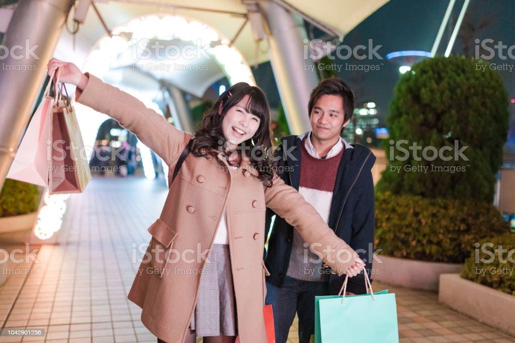 クリスマスの夜に買い物袋を持つ幸せな若いカップル ストックフォト