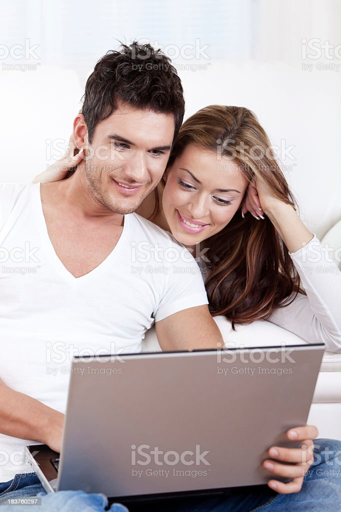 Happy young couple working on laptop royalty-free stock photo