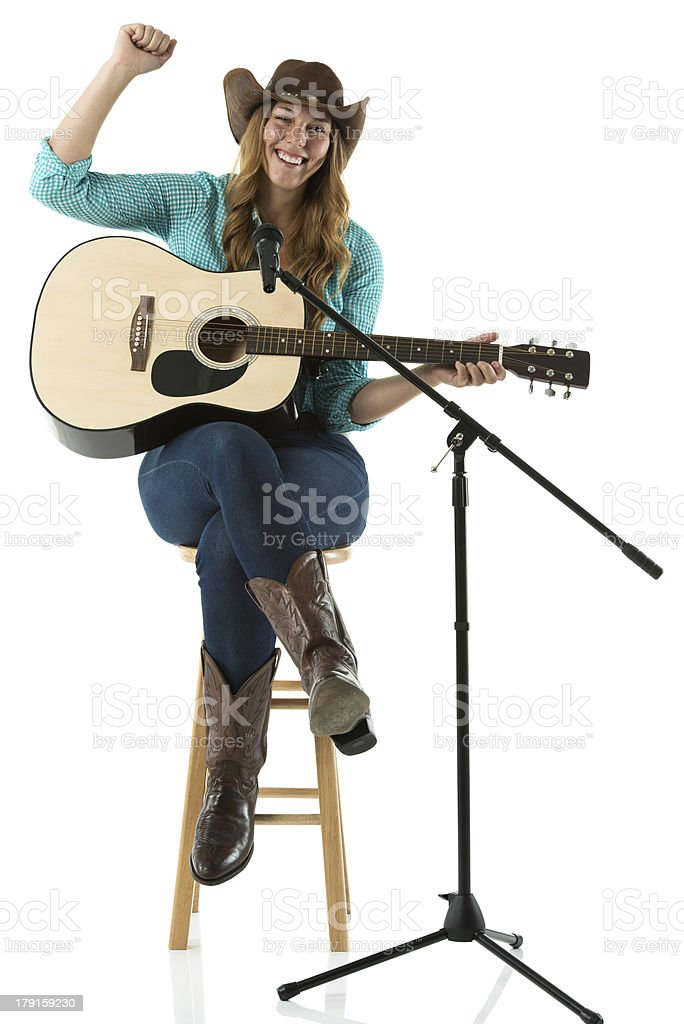 Happy young cowgirl sitting with a guitar royalty-free stock photo