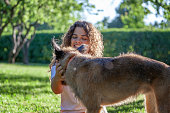 Happy young curly girl with a beautiful smile with her dog in the summer park.