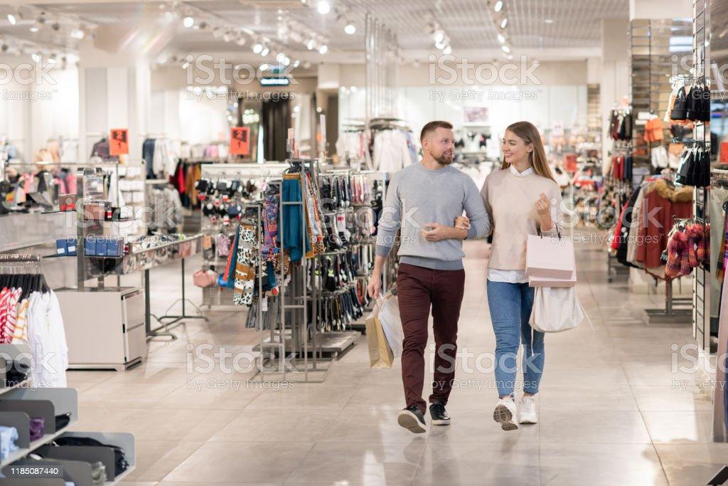 Glückliche junge Datteln tragen Papiertüten, während sie sich entlang der Bekleidungsabteilung bewegen - Lizenzfrei Architektur Stock-Foto
