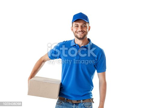 istock Happy young delivery man in blue uniform standing with parcel post box 1023438268