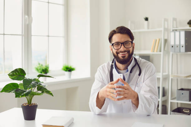 Happy young doctor giving online consultation to patient by video call from his office, copy space text stock photo