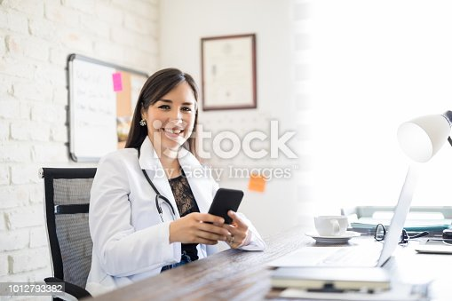 Portrait of cheerful female doctor sitting at her desk and using mobile phone
