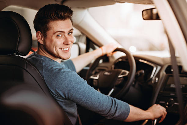 happy young driver behind the wheel of a car. buying a car and driving concept. - used car selling stock pictures, royalty-free photos & images