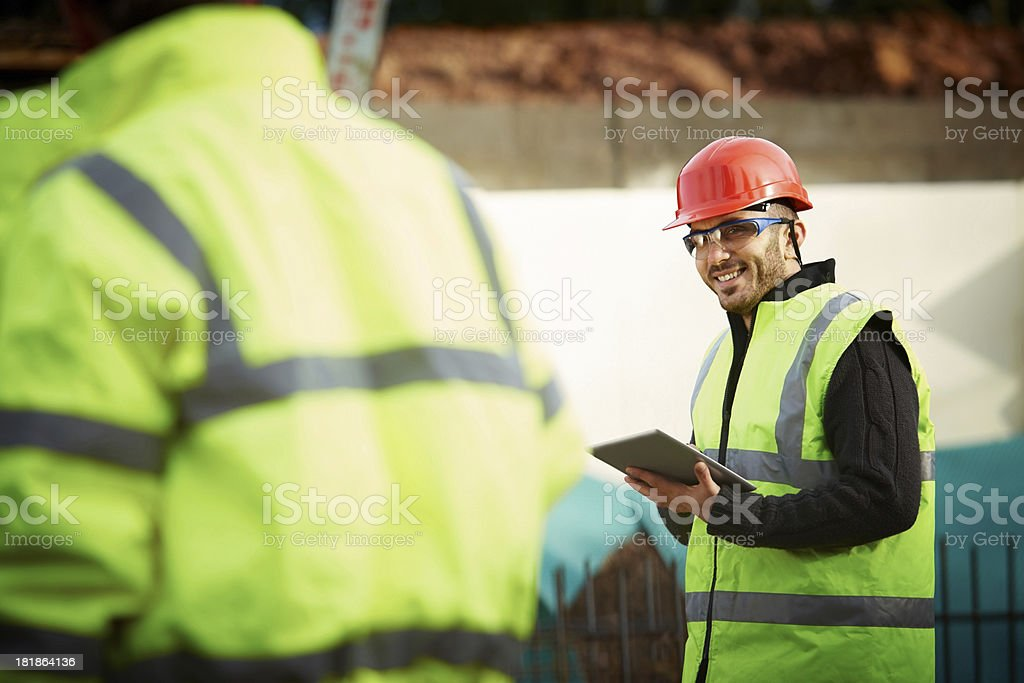 Happy young engineer with digital tablet at site stock photo