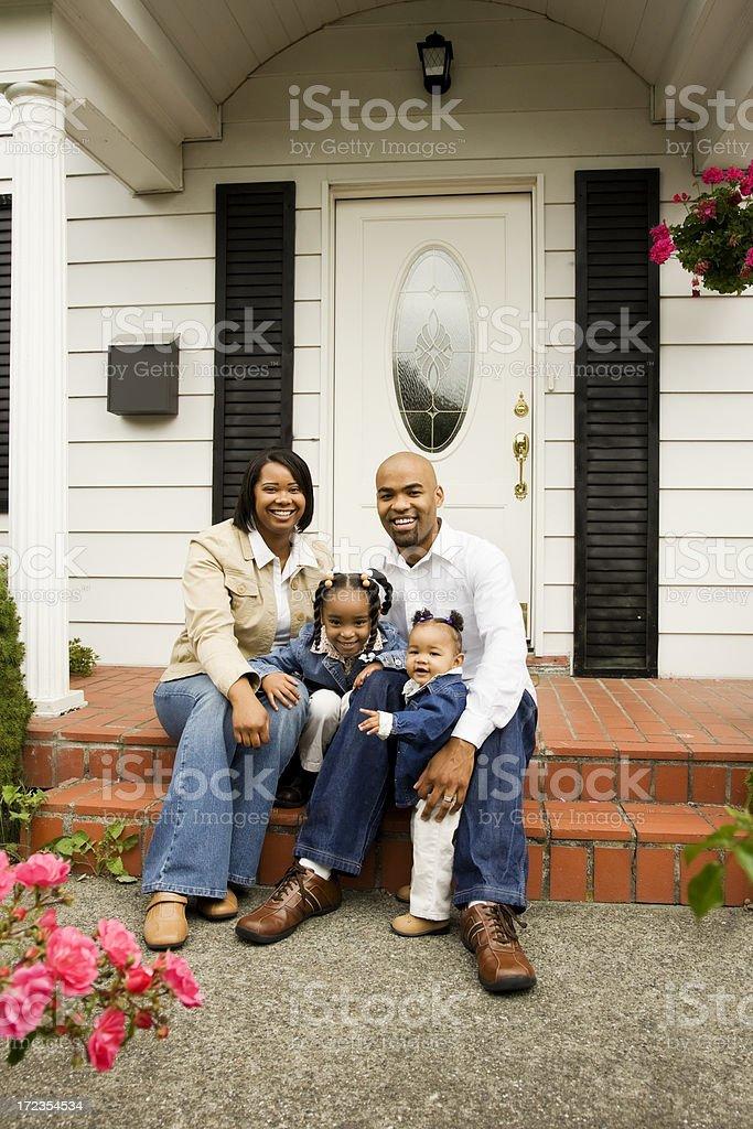 Familia joven feliz en casa en el porche de entrada foto de stock libre de derechos