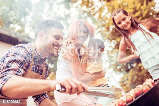 istock Happy young family barbecuing meat on the grill 816295582