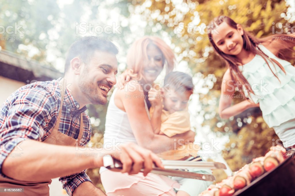 Happy young family barbecuing meat on the grill stock photo