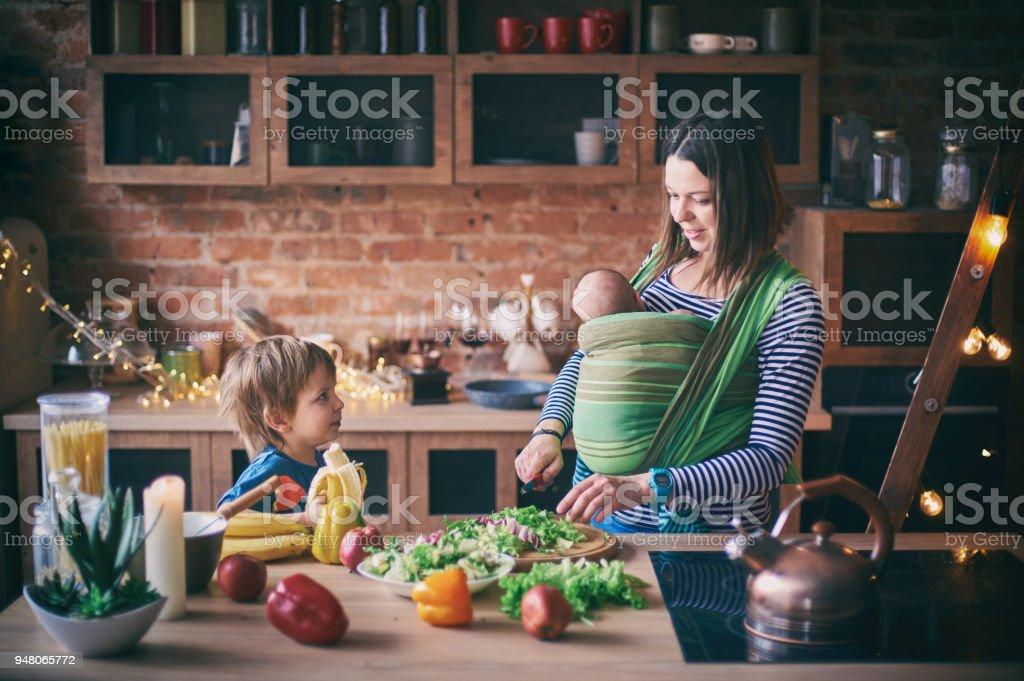 Familia joven feliz, hermosa madre con dos hijos, niño preescolar adorable y bebé en el sling cocinar juntos en una cocina soleada. - foto de stock
