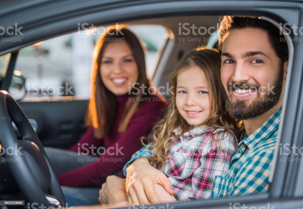 Happy young family buying their new car. stock photo