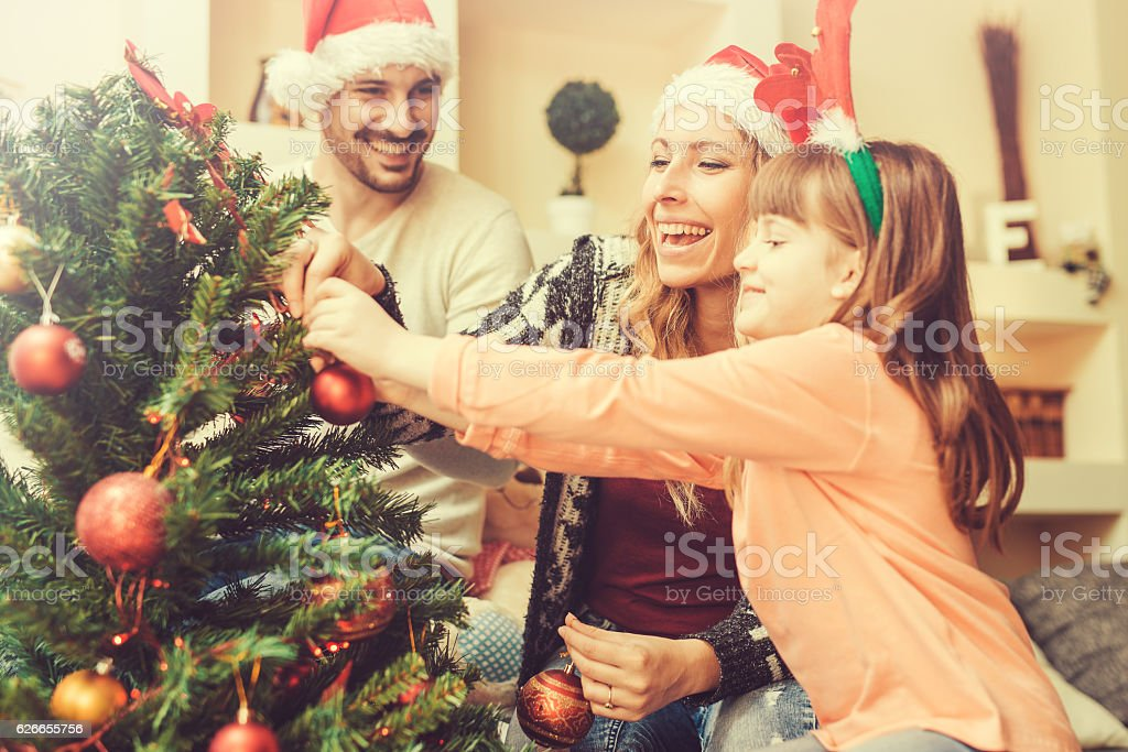Happy young family decorating a Christmas tree stock photo