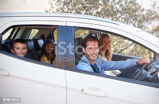 829619540 istock photo Happy young family driving in their car looking to camera 829619442