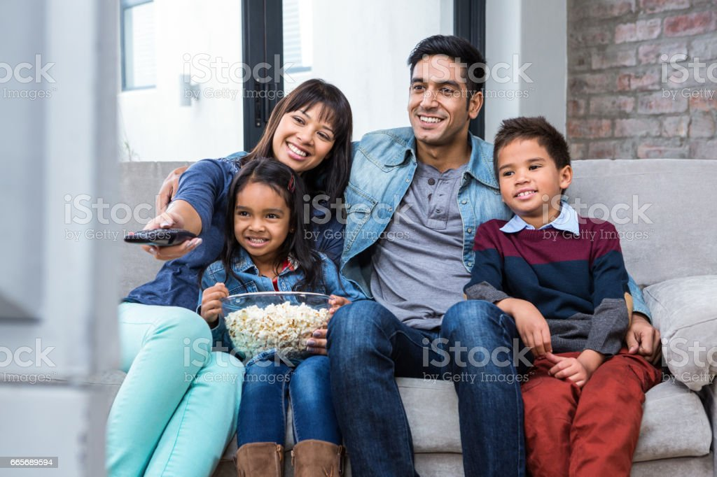 Happy young family eating popcorn while watching tv stock photo