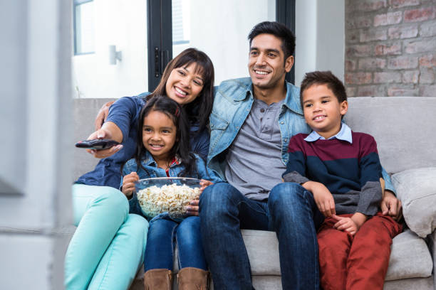 happy young family eating popcorn while watching tv - family watching tv stock photos and pictures
