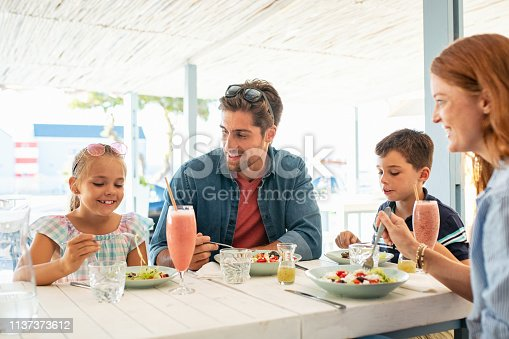 Cheerful family in restaurant enjoying lunch together in a patio. Mother and father observing daughter while eating food with son busy in eating. Smiling family with two children eating brunch together at kiosk during summer vacation.