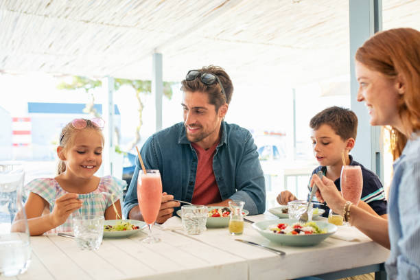 feliz familia joven disfrutando del almuerzo al aire libre - couple lunch outdoors fotografías e imágenes de stock