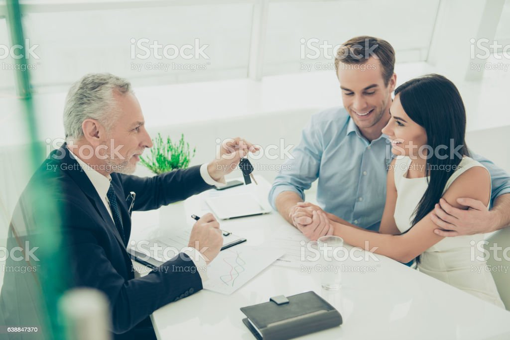 Happy young family getting keys from their new house stock photo