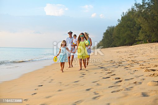 849648098 istock photo Happy young family have fun on beach run and jump 1164523988
