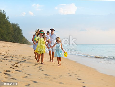 849648098 istock photo Happy young family have fun on beach run and jump 1164524114