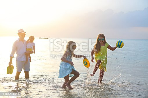 147878016 istock photo Happy young family have fun on beach run and jump 1164526232