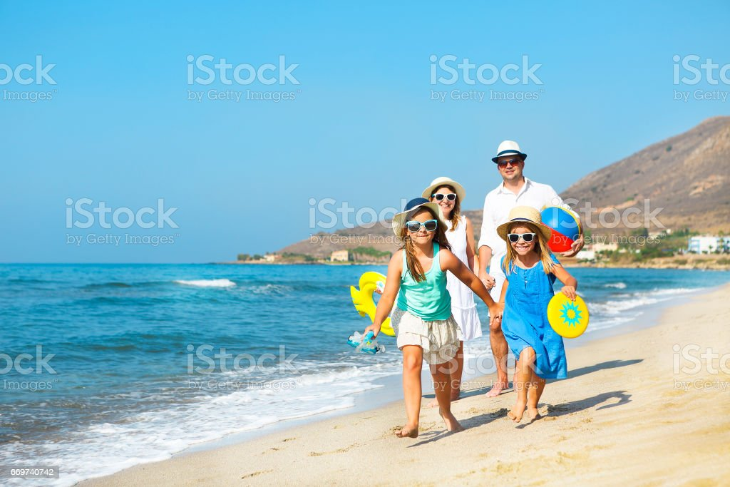 Happy young family having fun running on beach at sunset. Family traveling concept - fotografia de stock