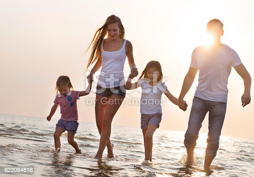 849648098 istock photo Happy young family having fun running on beach at sunset 622064816